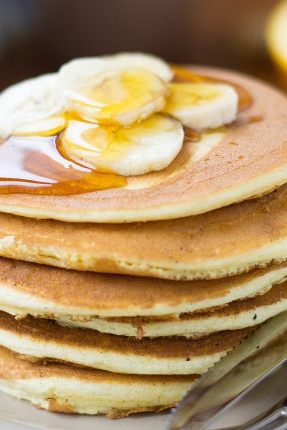 Stack of pancakes topped with bananas