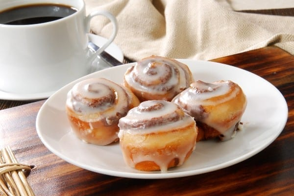 4 Weight Watchers Easy Mini Cinnamon Rolls on a white plate with a cup of coffee in the background.