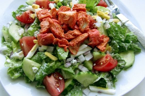 Weight Watchers Buffalo Chicken on top of a salad, on a white plate.