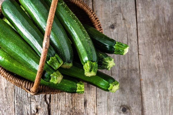 Zucchini in a basket on a wooden background